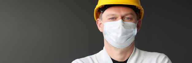 Männlicher bauarbeiter in gelber kaste und medizinischer schutzmaske. coronavirus-pandemie-konstruktionskonzept