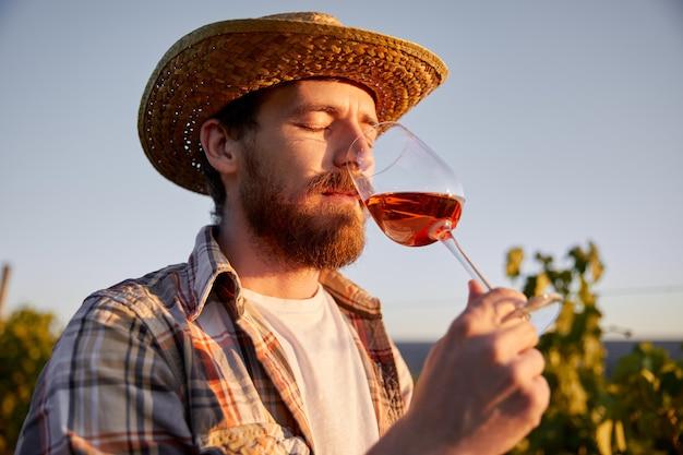 Männlicher bauer, der wein auf weinberg trinkt