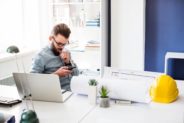 Männlicher bauingenieur, der im büro unter verwendung des mobiltelefons sitzt