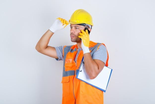 Männlicher baumeister, der am telefon mit hand auf helm in uniform, handschuhen, vorderansicht spricht.