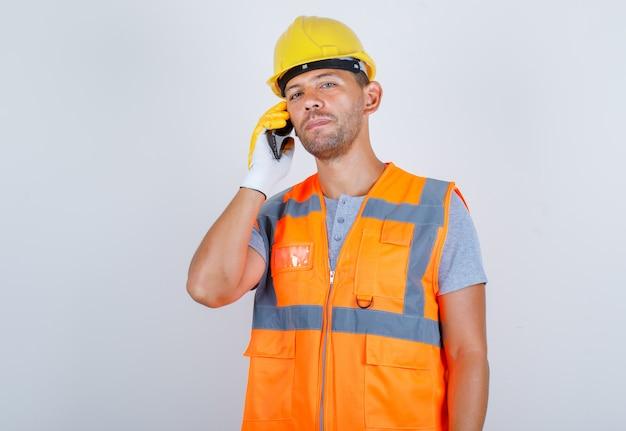 Männlicher baumeister, der auf handy in uniform, helm, handschuhen, vorderansicht spricht.