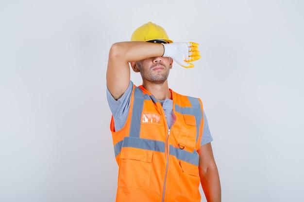 Männlicher baumeister, der augen mit arm in uniform, helm, handschuhen bedeckt und ernsthafte und traurige vorderansicht schaut.