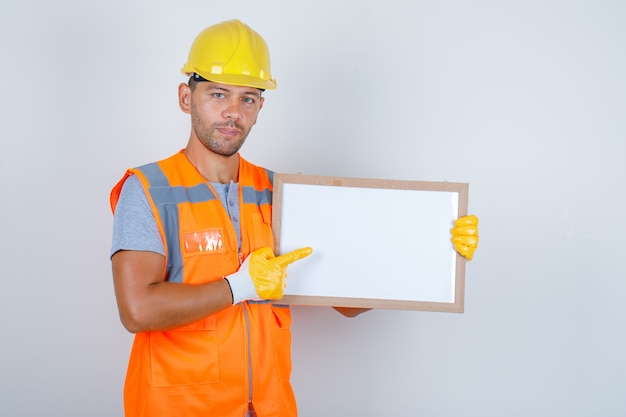 Männlicher baumeister, der etwas auf der weißen tafel in der vorderansicht der uniform, des helms, der handschuhe zeigt.