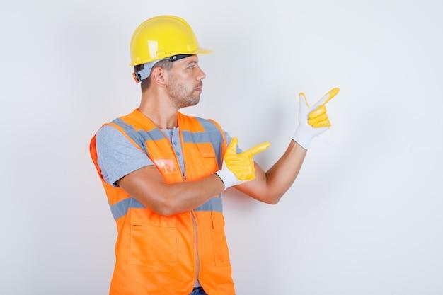 Männlicher baumeister, der finger auf etwas in uniform zeigt und selbstbewusst, vorderansicht schaut