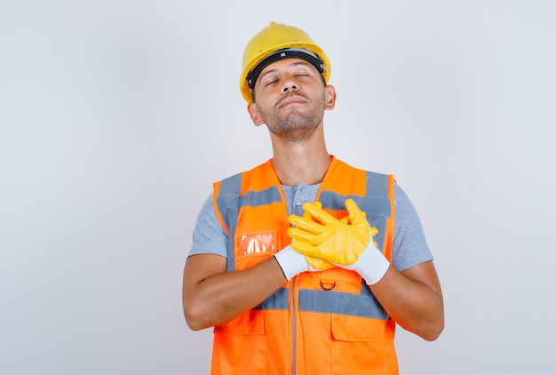Männlicher baumeister, der hände auf herz in uniform, helm, handschuhen hält und dankbar schaut, vorderansicht