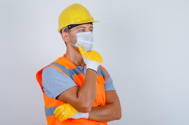 Männlicher baumeister, der in uniform, helm, maske, handschuhen vorderansicht denkt und wegschaut.