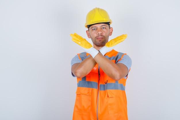 Männlicher baumeister, der kein zeichen mit verschränkten armen in uniform, helm, handschuhen, vorderansicht gestikuliert.
