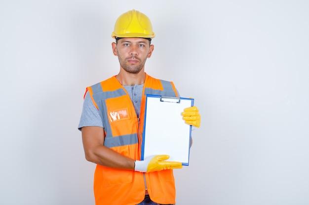 Männlicher baumeister, der klemmbrett hält und kamera in uniform, helm, handschuhen vorderansicht betrachtet.
