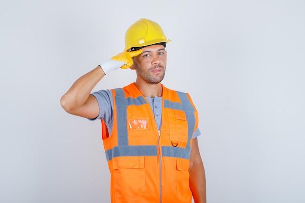Männlicher baumeister, der mit dem finger gegen seine schläfe in der vorderansicht der uniform, des helms, der handschuhe gestikuliert.