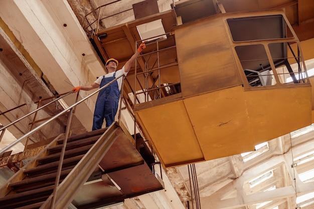 Männlicher baumeister, der oben auf der treppe steht