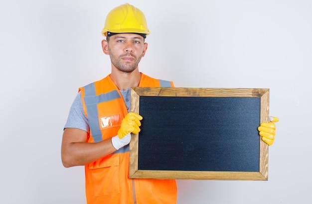 Männlicher baumeister, der tafel in uniform, helm, handschuhe, vorderansicht hält.