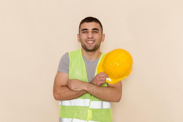 Männlicher baumeister der vorderansicht, der gelben helm hält, der auf hellem hintergrund lächelt und aufwirft