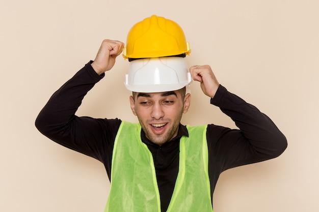 Männlicher baumeister der vorderansicht, der zwei helme auf hellem hintergrund trägt