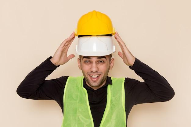 Männlicher baumeister der vorderansicht, der zwei helme trägt, die auf hellem hintergrund lächeln