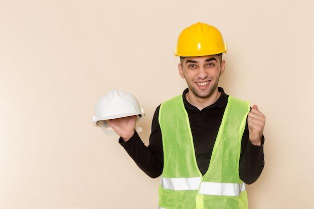 Männlicher baumeister der vorderansicht im gelben helm, der einen anderen helm auf hellem hintergrund hält
