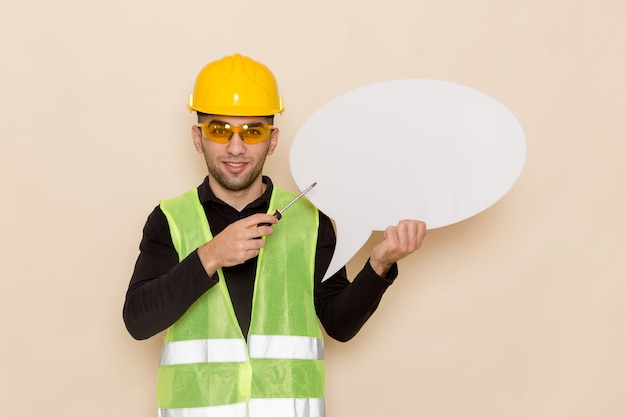 Männlicher baumeister der vorderansicht im gelben helm, der großes weißes zeichen auf dem hellen hintergrund hält