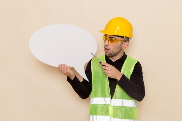 Männlicher baumeister der vorderansicht im gelben helm, der großes weißes zeichen auf hellem schreibtisch hält