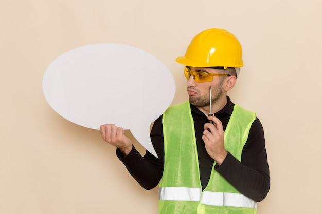 Männlicher baumeister der vorderansicht im gelben helm, der großes weißes zeichen hält, das auf hellem hintergrund denkt