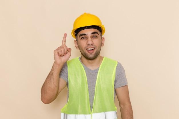 Männlicher baumeister der vorderansicht im gelben helm, der mit erhobenem finger auf dem hellen hintergrund aufwirft