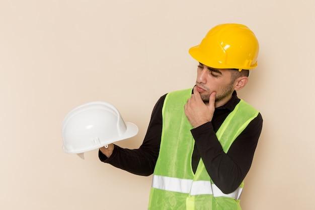 Männlicher baumeister der vorderansicht im gelben helm, der weißen helm auf hellem hintergrund hält