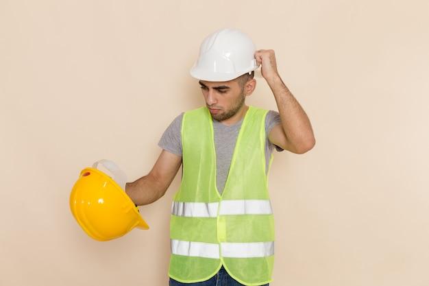 Männlicher baumeister der vorderansicht im weißen helm, der auf hellem hintergrund aufwirft