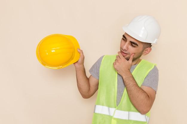 Männlicher baumeister der vorderansicht im weißen helm, der gelben auf dem cremefarbenen hintergrund hält
