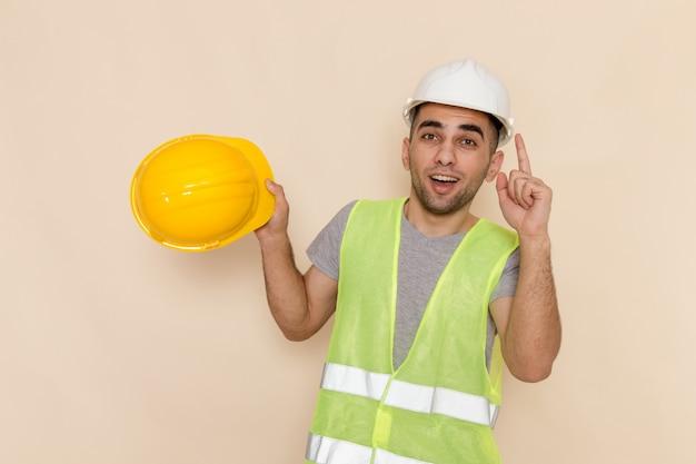 Männlicher baumeister der vorderansicht im weißen helm, der gelben helm auf dem cremefarbenen hintergrund hält