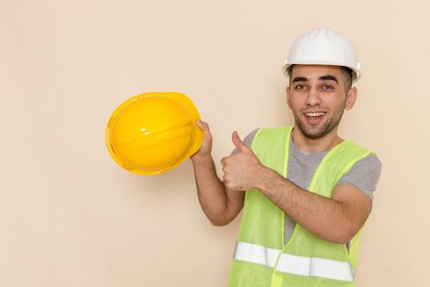 Männlicher baumeister der vorderansicht im weißen helm, der gelben helm auf dem hellen hintergrund hält