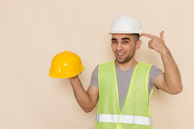 Männlicher baumeister der vorderansicht im weißen helm, der gelben helm auf hellem schreibtisch hält