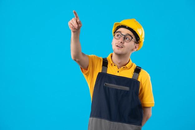 Männlicher baumeister der vorderansicht in der gelben uniform auf blau