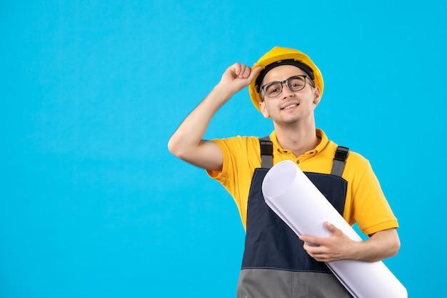 Männlicher baumeister der vorderansicht in der gelben uniform mit papierplan auf blau