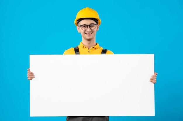 Männlicher baumeister der vorderansicht in der gelben uniform mit plan auf blau