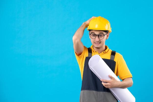 Männlicher baumeister der vorderansicht in der gelben uniform und im helm auf blau