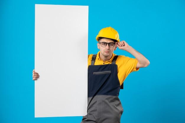 Männlicher baumeister der vorderansicht in der uniform mit papierplan auf blau