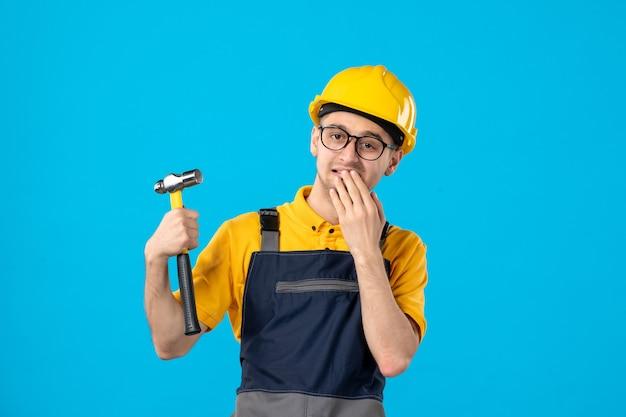 Männlicher baumeister der vorderansicht in uniform und helm mit hammer auf blau