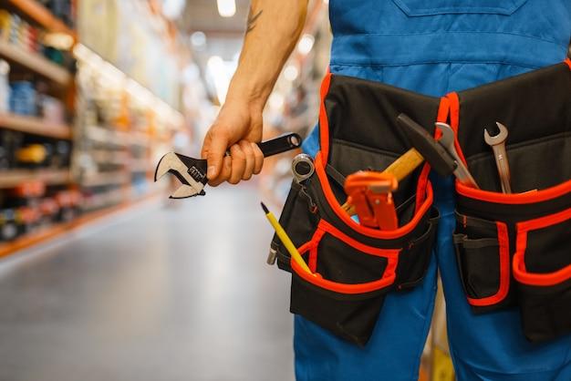 Männlicher baumeister, der werkzeuggürtel am regal im baumarkt wählt. konstrukteur in uniform betrachten die waren in diy shop