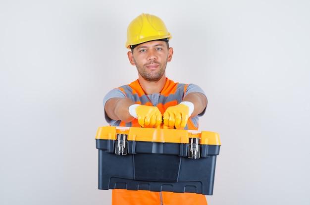 Männlicher baumeister, der werkzeugkasten hält und kamera in uniform, helm, handschuhe, vorderansicht betrachtet.