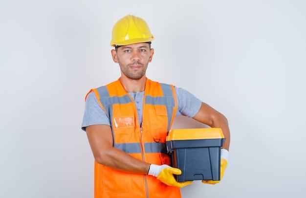 Männlicher baumeister, der werkzeugkasten in uniform, helm, handschuhe, vorderansicht hält.