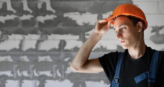 Männlicher baumeister in arbeitskleidung und einem orangefarbenen schutzhelm gekleidet. nahaufnahmeportrait