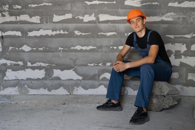 Männlicher baumeister in arbeitskleidung und einem orangefarbenen schutzhelm gekleidet. setzen sie sich auf einen stein, um sich auszuruhen. platz kopieren