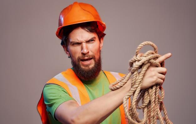 Männlicher baumeister in der orangefarbenen schutzhelmarbeitsermüdungsindustrie