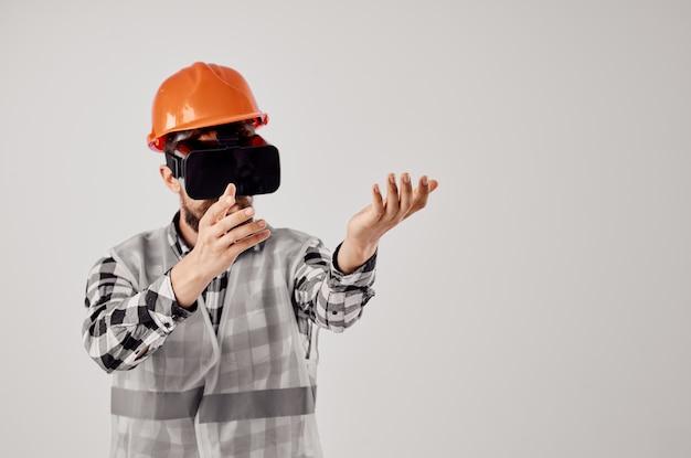 Männlicher baumeister in einem orangefarbenen helmtechnologie-profi isolierten hintergrund