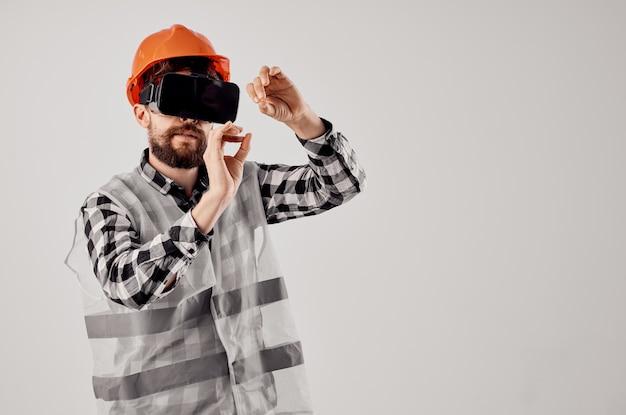Männlicher baumeister in einem professionellen hellen hintergrund der orange helmtechnologie
