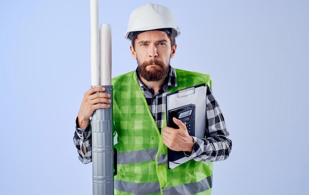 Männlicher baumeister in einem weißen helm blaupausen professionellen blauen hintergrund