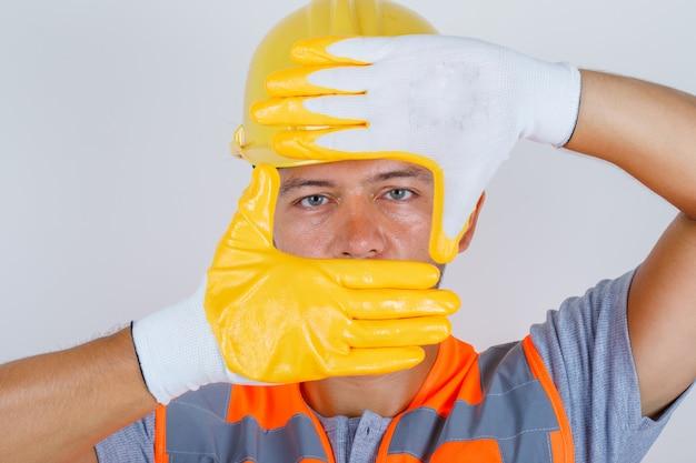 Männlicher baumeister in uniform, die durch rahmen schaut, gebildet durch hände, vorderansicht.