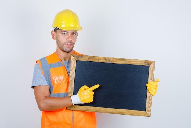 Männlicher baumeister in uniform, helm, handschuhe, die etwas auf tafel zeigen, vorderansicht.