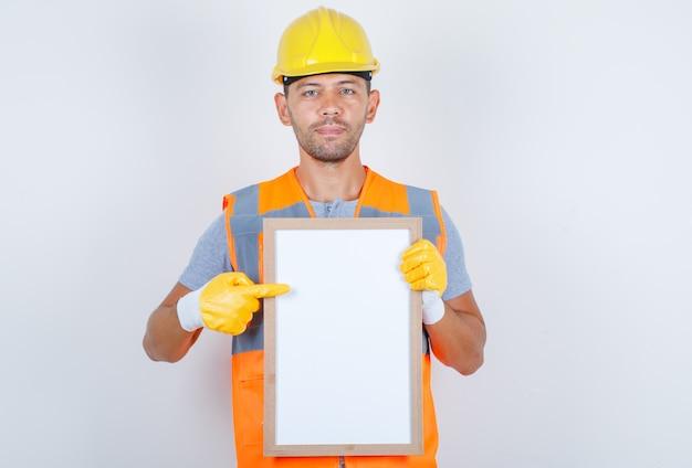 Männlicher baumeister in uniform, helm, handschuhe, die etwas auf weißer tafel zeigen, vorderansicht.