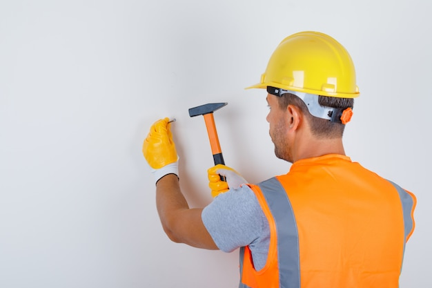 Männlicher baumeister in uniform, helm, handschuhe, die nagel in wand hämmern, rückansicht.
