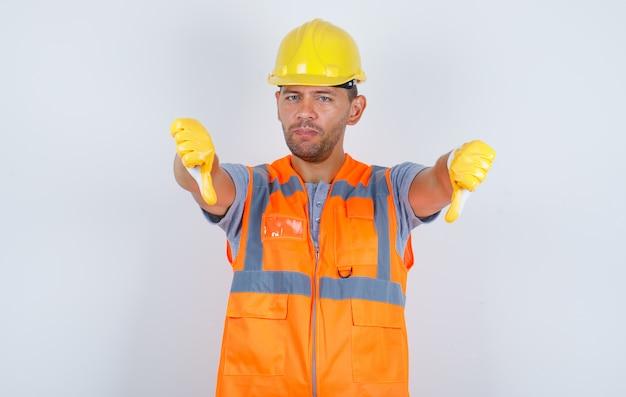 Männlicher baumeister zeigt daumen nach unten in uniform, helm, handschuhen und verärgert, vorderansicht
