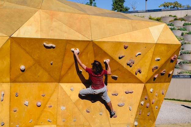 Männlicher bergsteiger, der einen schwierigen weg zur sonne auf einer kletterwand im freien versucht